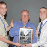 Stat Bowl team winners Bard Barney (left) and Brian Hartman of Texas A&M with moderator Michael Anderson (center)