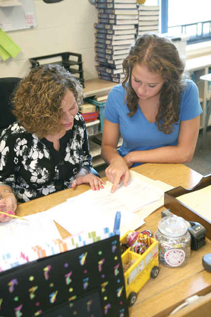 Nancy Lassiter (left) reviews sample exam questions with Hannah Bultman, one of her AP Statistics students.