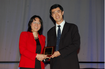 Xihong Lin presents the COPSS Presidents' Award to Samuel Kou.