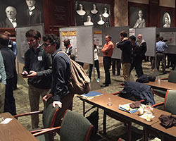 Attendees visit the 25 presentations at the poster session during the Fall Research Conference.