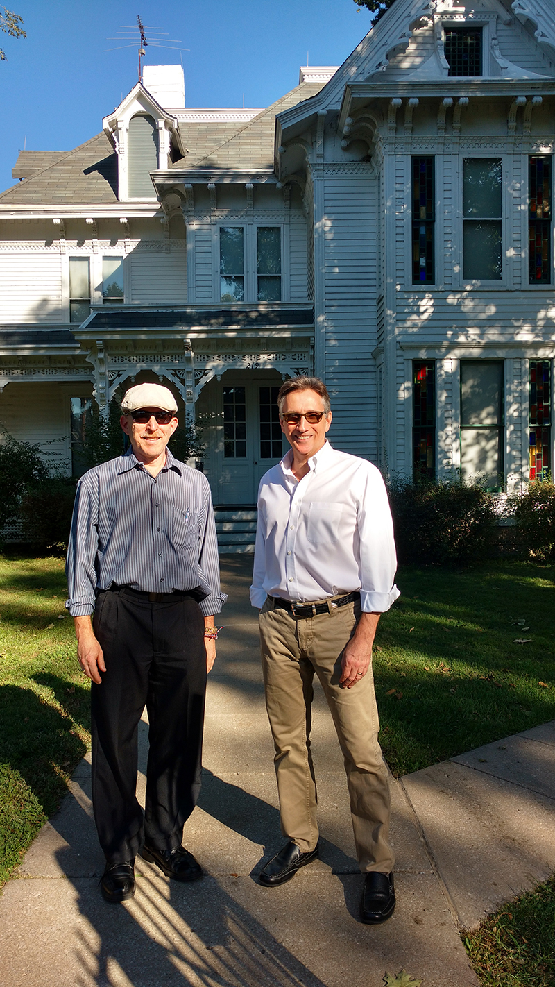 Terry Katz (wearing hat) stands next to Clifton Truman Daniel, the oldest grandson of President Harry Truman, in front of the Truman home in Independence, Missouri.