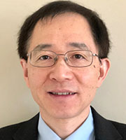 Photo shows Xuming He, an Asian man wearing thin-rimmed silver glasses with short dark hair, a suit jacket, and a light blue collar.